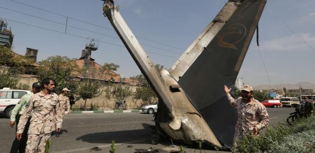 Integrante da Guarda Revolucionária do Irã observa parte de avião que caiu perto do aeroporto de Teerã