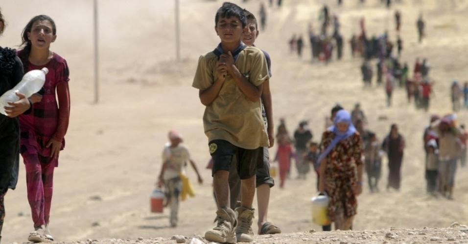 11.ago.2014 - Crianças iraquianas da comunidade yazidi atravessam a fronteira entre Iraque e Síria. Cerca de 20 mil civis conseguiram escapar do cerco dos jihadistas do Estado Islâmico em torno do monte Sinjar, no norte do Iraque, onde estavam em água e comida
