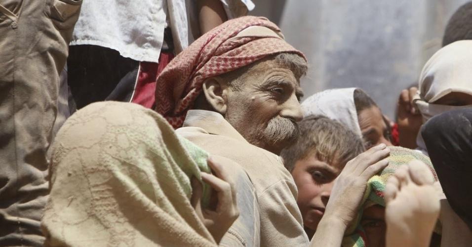 11.ago.2014 - Deslocados iraquianos da comunidade yazidi atravessam a fronteira entre Iraque e Síria. Cerca de 20 mil civis pertencentes conseguiram escapar do cerco dos jihadistas do Estado Islâmico em torno do monte Sinjar, no norte do Iraque, onde estavam em situação desesperada por falta de água e comida