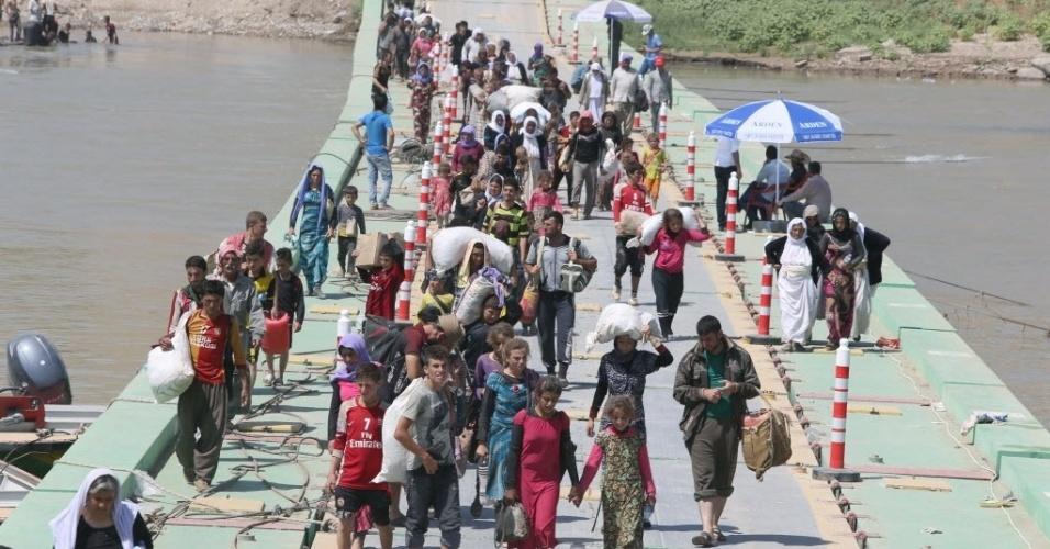 11.ago.2014 - Deslocados iraquianos da comunidade yazidi atravessam a fronteira entre Iraque e Síria. O grupo decidiu voltar ao Iraque após os ataques aéreos dos EUA contra a organização Estado Islâmico