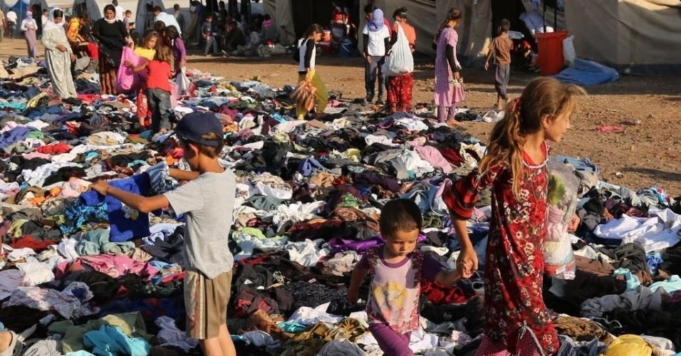 12.ago.2014 - Refugiados iraquianos membros da minoria étnica yazidi selecionam roupas doadas por uma organização de caridade no campo de Nowruz, na Síria, nesta terça-feira (12). Os refugiados ganharam novos heróis: combatentes curdos sírios que lutam contra militantes islâmicos para esculpir uma rota de fuga para dezenas de milhares presos no topo da montanha. Militares americanos e iraquianos também ajudam lançando comida e água para o grupo yazidi
