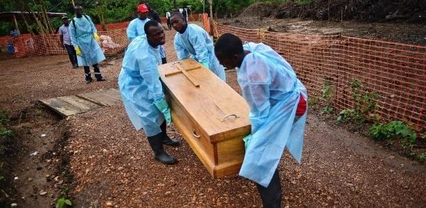 Coveiros usam luvas e roupas de proteção para carregar corpos das vítimas de ebola em Serra Leoa