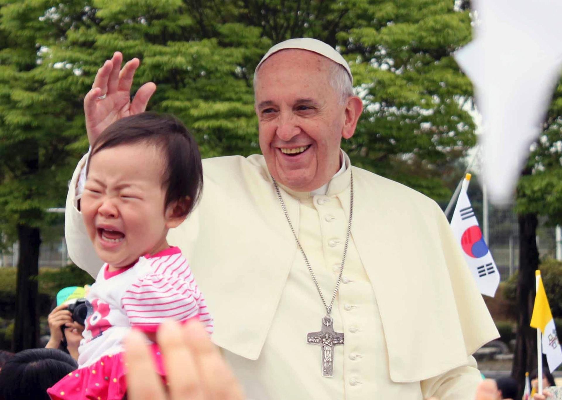 15.ago.2014 - Criança chora após ser abençoada pelo papa Francisco durante missa no Estádio da Copa do Mundo de Daejeon, na Coreia do Sul. Ele conduziu a missa em lembrança das mais de 300 pessoas mortas no naufrágio de uma balsa em abril. É a primeira visita em 15 anos de um pontífice ao país, onde vivem cerca de 5 milhões de católicos
