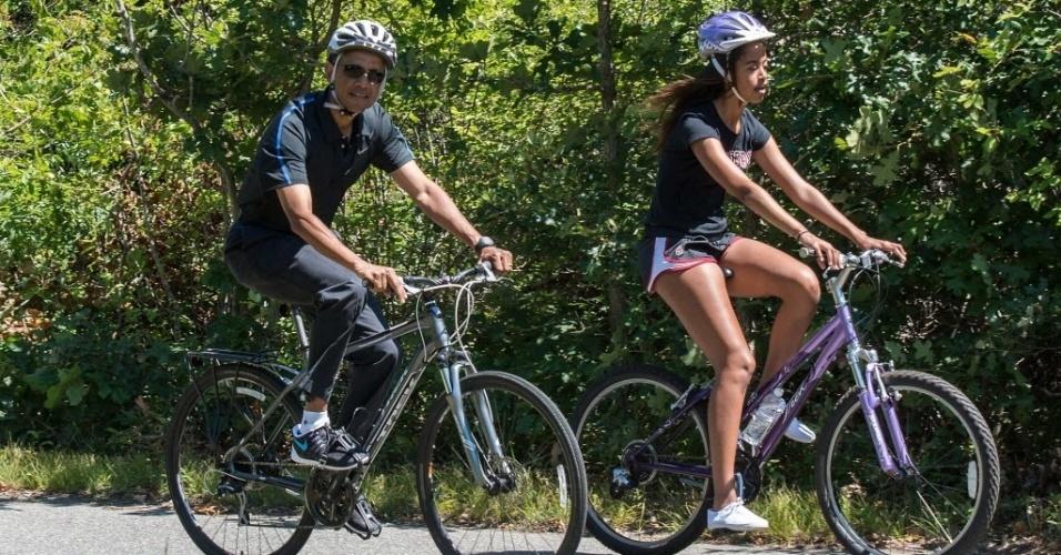 15.ago.2014 - O presidente dos Estados Unidos, Barack Obama, anda de bicicleta com a filha Malia, em Martha Vineyard, Massachusetts (EUA), nesta sexta-feira (15), durante férias anuais de verão na ilha