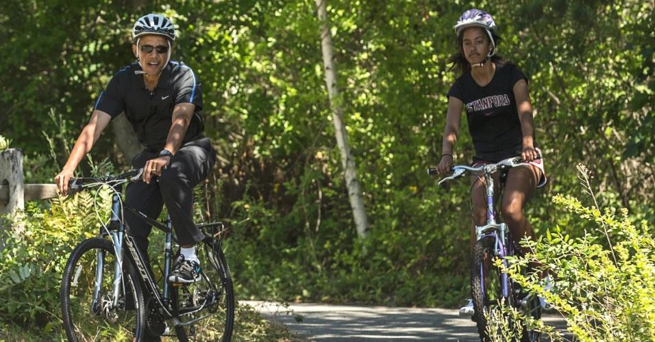 16.ago.2014 - O presidente dos Estados Unidos, Barack Obama, anda de bicicleta com sua filha Malia durante viagem de férias na vinícola Martha, em Massachusetts. A foto, tirada na sexta-feira (15), foi divulgada nesta sábado (16)