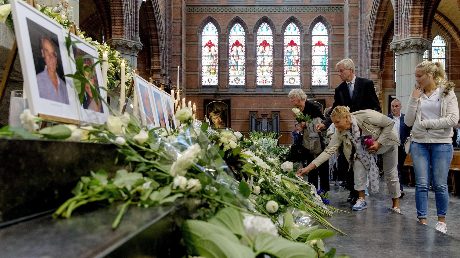 17.ago.2014 - Visitantes colocam flores no altar da igreja Sint-Vitus, em Hilversum, na Holanda, próximo às fotos das vítimas do voo MH17 da Malaysia Airlines, que foi derrubado no leste da Ucrânia no dia 17 de julho. Um mês após a tragédia do voo MH17 no leste da Ucrânia, ainda há um longo esforço de investigação pela frente, sobretudo na Holanda - país de origem da maioria das vítimas