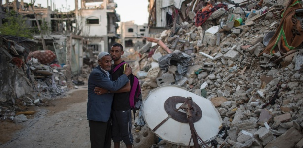 Nader al-Masri, atleta olímpíco palestino, abraça o pai diante do que sobrou da casa onde moravam Beit Hanoun, na Faixa de Gaza