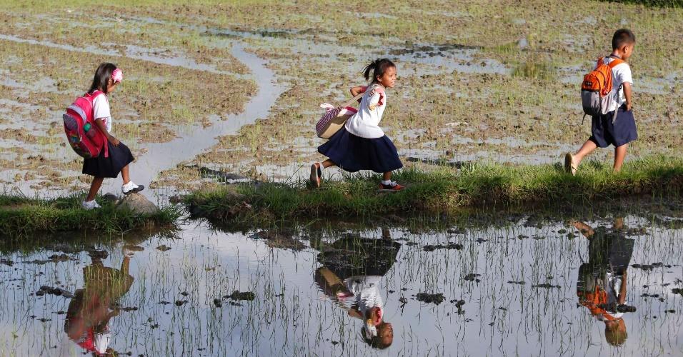 19.ago.2014 - Crianças filipinas precisam caminhar mais de 2 km entre os arrozais para ir de casa até a escola