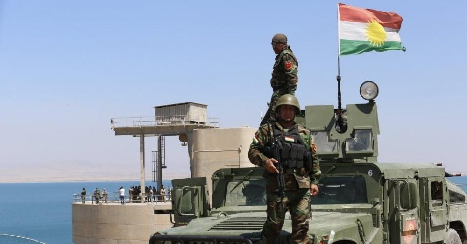 21.ago.2014 - Combatentes fazem patrulha em um veículo com uma bandeira curda na represa de Mosul, no norte do Iraque. Apesar das falhas estruturais, a maior barragem do país com 3,6 km de extensão, construída por um consórcio alemão-italiano na década de 1980, é fonte vital de energia para Mosul, a maior cidade do norte do Iraque com  1,7 milhões de habitantes. Os insurgentes do Estado Islâmico havia tomado o controle da barragem nas últimas semanas. As forças iraquianas e curdas conseguiram retomar o controle do local com a ajuda de ataques aéreos dos EUA