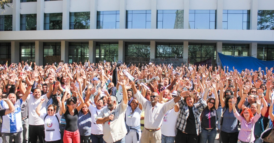 21.ago.2014 - Funcionários em greve da USP (Universidade de São Paulo) realizam assembleia em frente ao prédio da reitoria na Cidade Universitária, nesta quinta-feira (21). Uma audiência de conciliação realizada no TRT (Tribunal Regional do Trabalho) com representantes da USP e do Sintusp (sindicato dos servidores da universidade) terminou sem acordo nesta quarta-feira (20). Os servidores estão em greve desde o fim de maio, após anúncio de congelamento de salários feito pela universidade. O reitor, Marco Antonio Zago, informou que a instituição fará um investimento inicial de até R$ 400 milhões em programa de demissão voluntária, caso ele seja aprovado