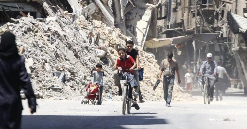 25.ago.2014 - Menino anda de bicicleta em rua repleta de escombros em Harasta, no subúrbio de Damasco. Três anos de conflito entre o governo de Bashar Assad e rebeldes deixou mais de 190 mil mortos. O governo sírio afirmou que tem de ser incluído na coordenação de qualquer ataque aéreo contra militantes islâmicos no país, depois que os Estados Unidos afirmaram considerar a possibilidade de combater o grupo Estado Islâmico dentro do território sírio