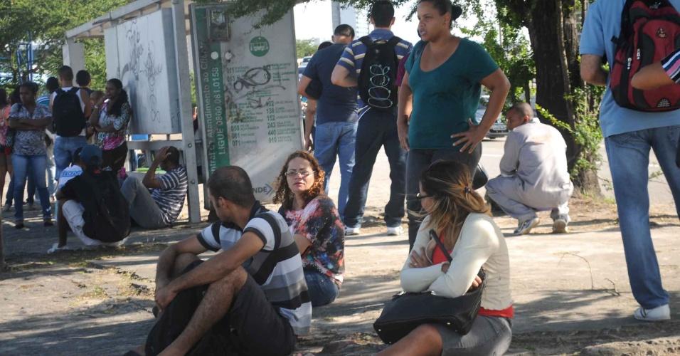 25.ago.2014 - Passageiros se sentam no chão enquanto aguardam ônibus em parada no Recife. Os rodoviários resolveram fazer uma paralisação na manhã desta segunda-feira (25) para pressionar o TST (Tribunal Superior do Trabalho) a reverter a decisão que suspendeu um aumento de 10% no salário da categoria negociado após greve em julho