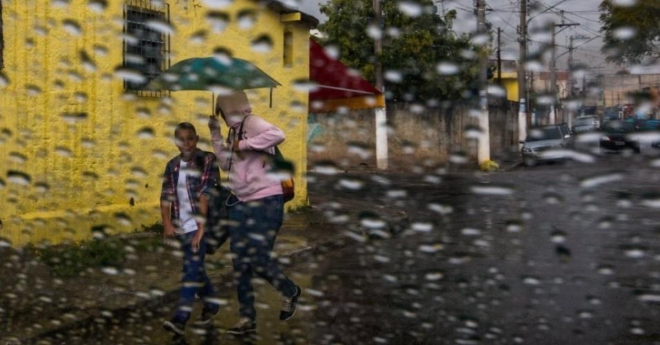 26.ago.2014 - Mulher e menino se protegem da chuva em Guaianazes, na zona leste de São Paulo, na tarde desta terça-feira (26). De acordo com o CGE (Centro de Gerenciamento de Emergências), apesar da chuva, o clima continuará abafado na cidade e a temperatura máxima prevista é de 27ºC