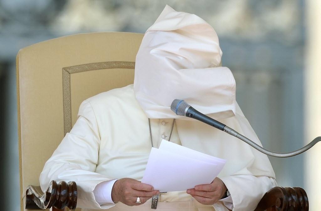 27.ago.2014 - Papa Francisco fica com o rosto coberto pela vestimenta durante a audiência geral semanal na praça de São Pedro, no Vaticano, nesta quarta-feira (27)