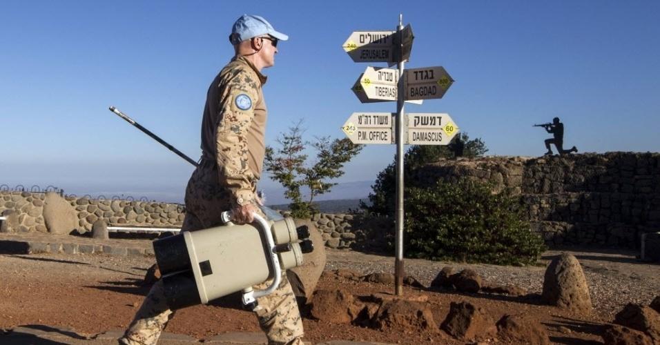 28.ago.2014 - Membro da ONU carrega binóculos para observar combates entre as forças leais ao ditador sírio, Bashar Assad, e os rebeldes em Quneitra, nesta quinta-feira (28). Os rebeldes sírios, incluindo um braço armado da Al Qaeda, tomaram o controle da fronteira da Síria com Israel
