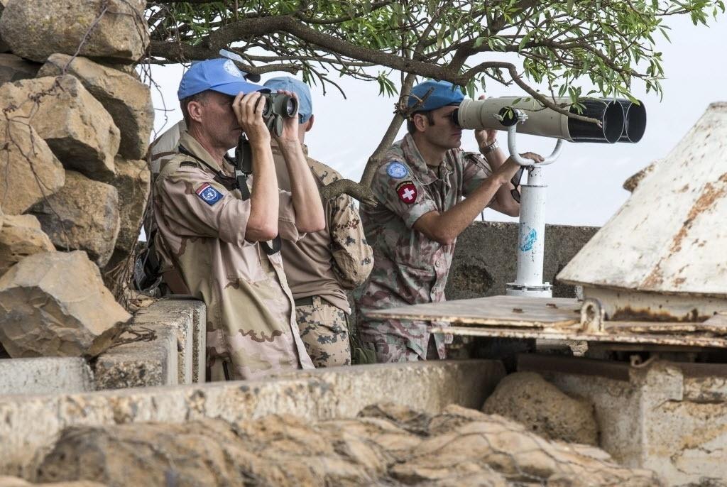 29.ago.2014 - Capacetes azuis da Força de Observadores da Nações Unidas(UNDOF), usam binóculos para observar movimentação no lado sírio das colinas do Golã, região ocupada por Israel desde a Guerra dos Seis Dias, em 1967. Rebeldes sírios da Al Nusra, ligados à Al Qaeda, tomaram área fronteiriça em Quneitra e capturaram 49 soldados das forças de paz da ONU