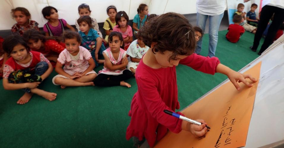 1º.set.2014 - Criança escreve durante aula em escola improvisada no campo de Bahrka, no Curdistão iraquiano