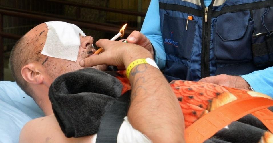 2.set.2014 - Um soldado ucraniano ferido acende um cigarro antes de ser levado por uma ambulância ao Hospital Militar de Kiev. O homem será transferido para a Alemanha, que concordou em tratar 20 militares feridos em confrontos com rebeldes pró-Rússia