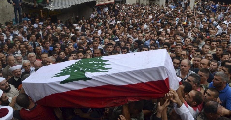 3.set.2014 - Parentes e soldados do exército libanês carregam o caixão do soldado Ali al Sayyed, que foi decapitado por militantes do EI (Estado Islâmico) no Arsal, durante funeral em Fnideq, no Líbano