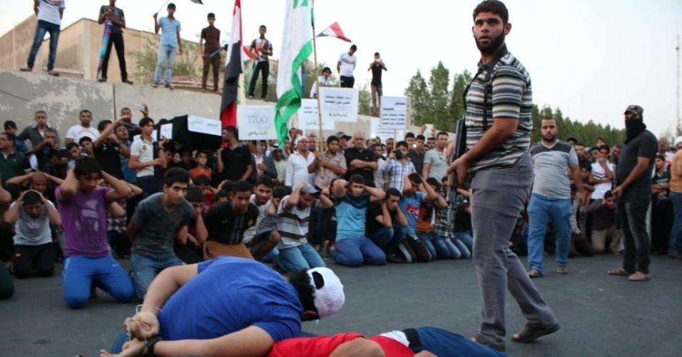3.set.2014 - Partidários do partido islâmico Al Fadila realizam uma simulação de execução durante um protesto para pedir justiça para os membros das forças iraquianas, que foram executados pelo Estado Islâmico (EI)