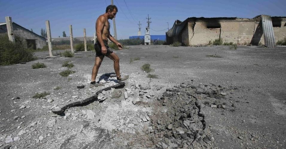 3.set.2014 - Um residente local passa por uma cratera causada por um bombardeio no vilarejo de Spartak fora Donetsk, na Ucrânia, nesta quarta-feira (3). A Ucrânia anunciou nesta quarta-feira (3) que seu presidente, Petro Poroshenko, chegou a um acordo com o presidente da Rússia, Vladimir Putin, para implementar um