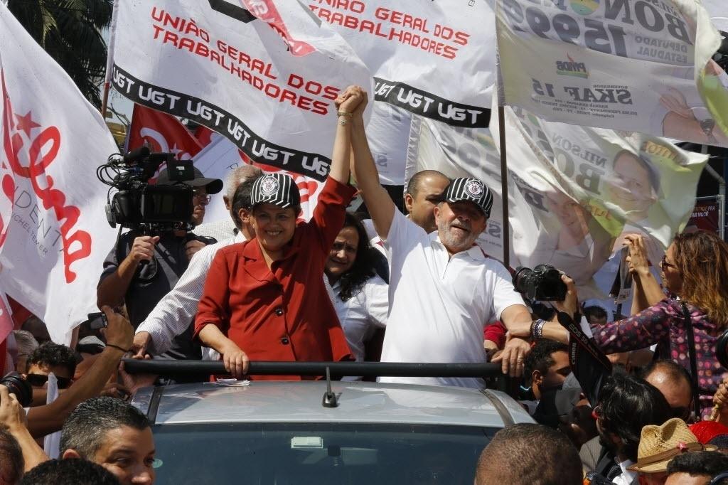 3.set.2014- A candidata a reeleição Dilma Roussef (PT) e o ex-presidente Luiz Inácio Lula da Silva colocam bonés do Corinthians durante carreata de campanha pelas ruas de São Bernardo do Campo, em São Paulo, na tarde da última terça-feira (2)