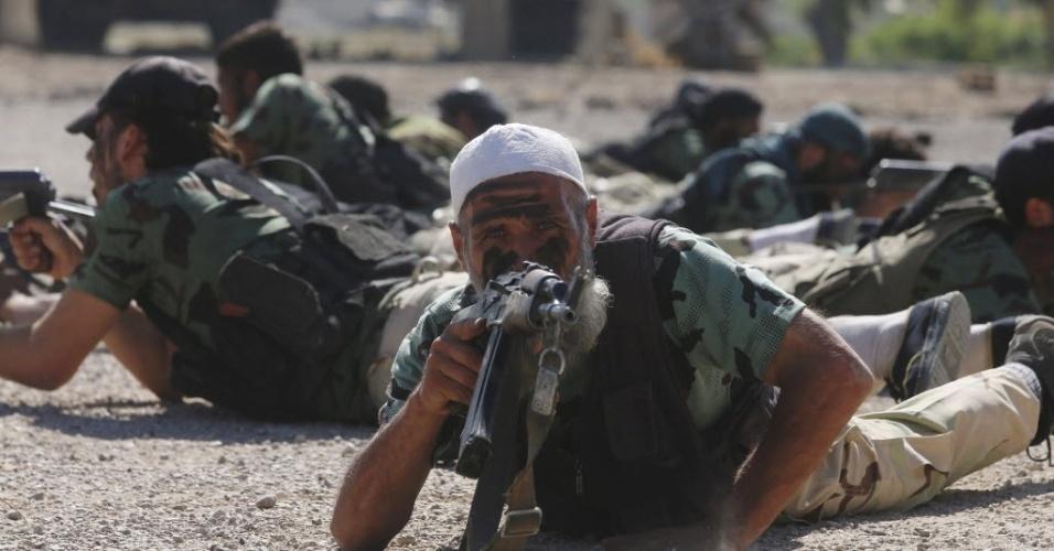 4.set.2014 - Combatente rebelde aponta arma durante uma exibição militar, como parte de uma cerimônia de formatura em um acampamento no leste da al Ghouta, perto de Damasco, na Síria. Os combatentes rebeldes recém-formados, que passaram por um treinamento militar, irão se juntar a brigada