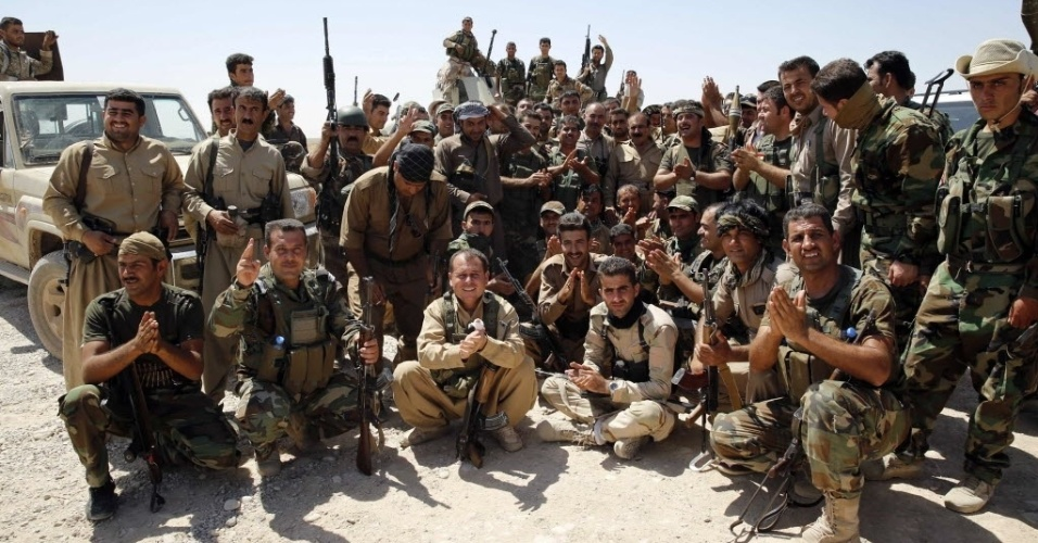 4.set.2014 - Combatentes curdos tiram foto para comemorar a retomada da aldeia Buyuk Yeniga, que antes estava sob controle do Estado Islâmico (EI)