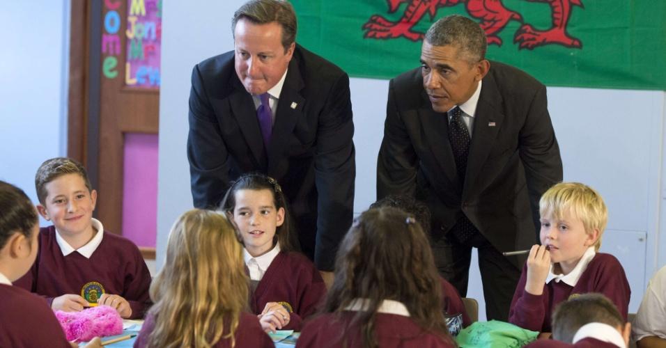 4.set.2014 - O primeiro-ministro britânico, David Cameron, e o presidente dos Estados Unidos, Barack Obama, conversam com crianças durante visita a escola em Newport, South Wales, no País de Gales, antes de participar da cúpula da Otan (Organização do Tratado do Atlântico Norte)