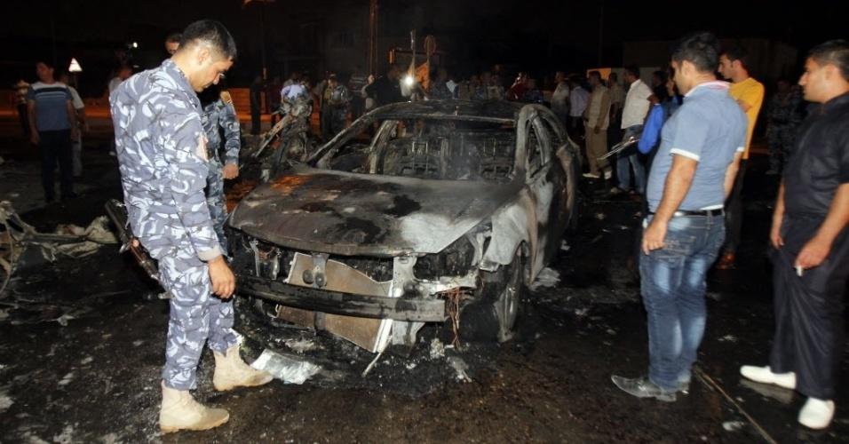 5.set.2014 - Policiais e moradores verificam local de explosão em frente a uma loja de bebidas no norte de Kirkuk, em Bagdá, no Iraque, na última quinta-feira (4). Um total de 15 pessoas foram mortas e 69 ficaram feridas em três atentados diferentes durante o dia ontem no Iraque, segundo fontes policiais