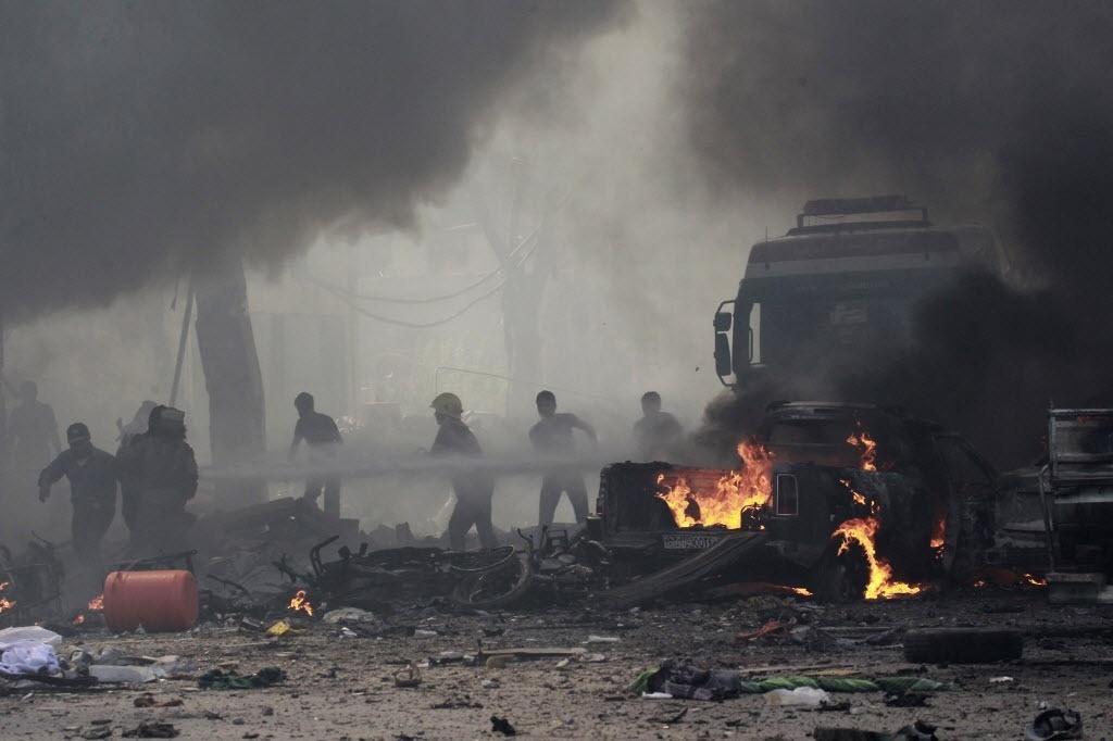 6.set.2014 - Moradores apagam incêndio causado por um ataque aéreo atribuído a forças leais ao presidente da Síria, Bashar al-Assad, próximo a um mercado de rua no centro de Raqqa