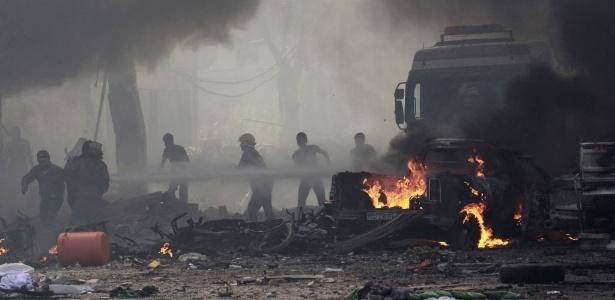 Moradores apagam incêndio causado por um ataque aéreo atribuído a forças leais ao presidente da Síria próximo a um mercado de rua no centro de Raqqa