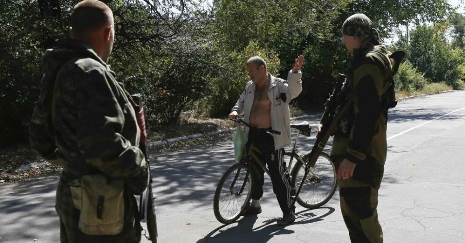 6.set.2014 - Separatistas pró-russos conversam com um morador local em um ponto de verificação na periferia de Donetsk, na Ucrânia, um dia depois de o governo do país e os rebeldes assinarem um acordo de cessar-fogo