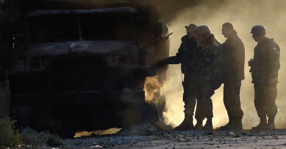 7.set.2014 - Soldados do exército ucraniano verificam um caminhão do exército queimado, após um ataque a bomba durante a noite, em um posto de controle do exército ucraniano na periferia da cidade de Mariupol. Tiros e bombardeios pesados ??abalaram a cidade durante a noite, aumentando os temores de que a trégua entre forças governamentais e rebeldes tenha acabado