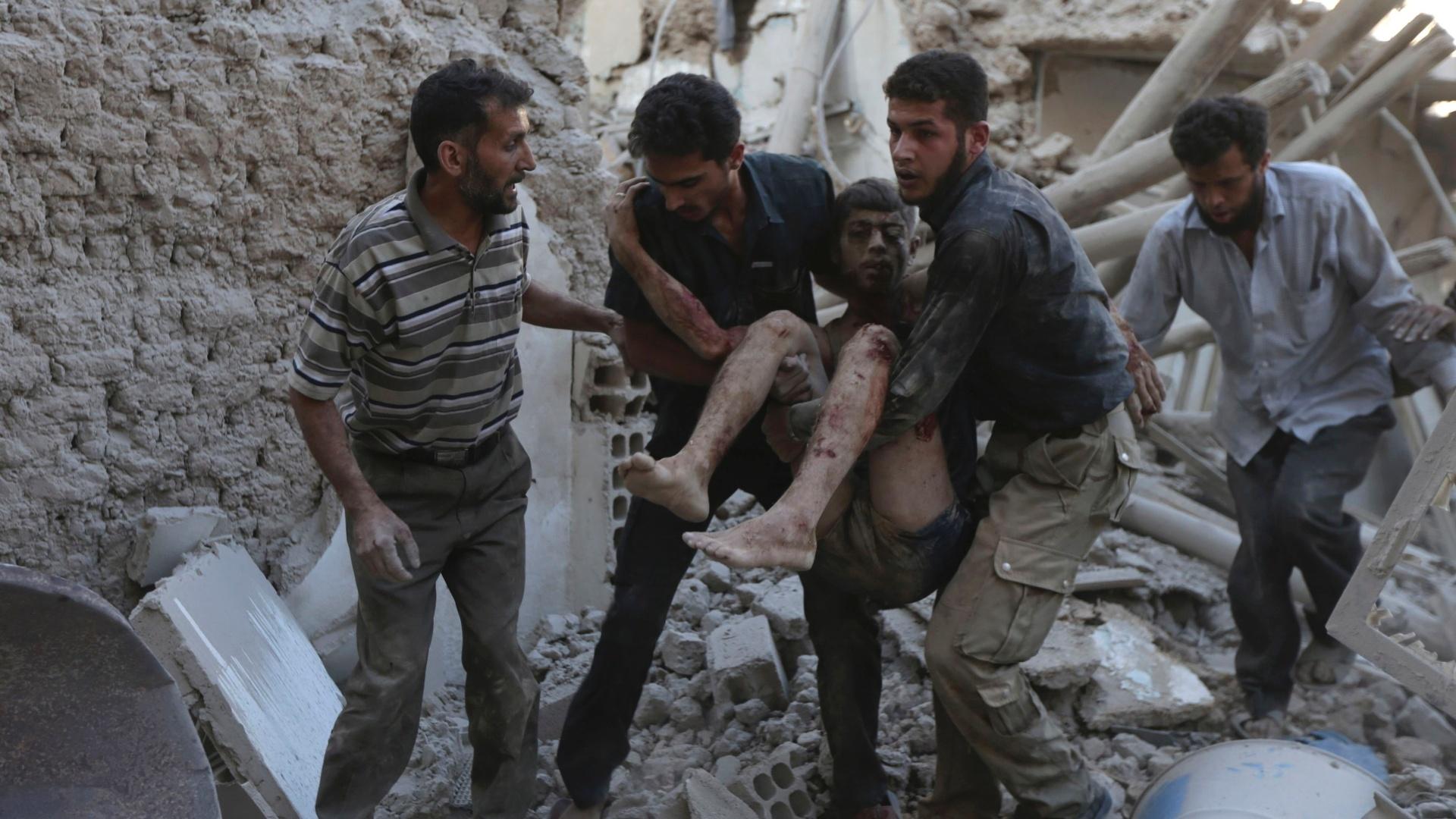 11.09.2014 - Homens carregam corpo de jovem ferido após ataques aéreos em Douma, na Síria, nesta quinta-feira (11). Ativistam afirmam que os ataques foram feitos por forças leais ao presidente do país, Bashar al-Assad