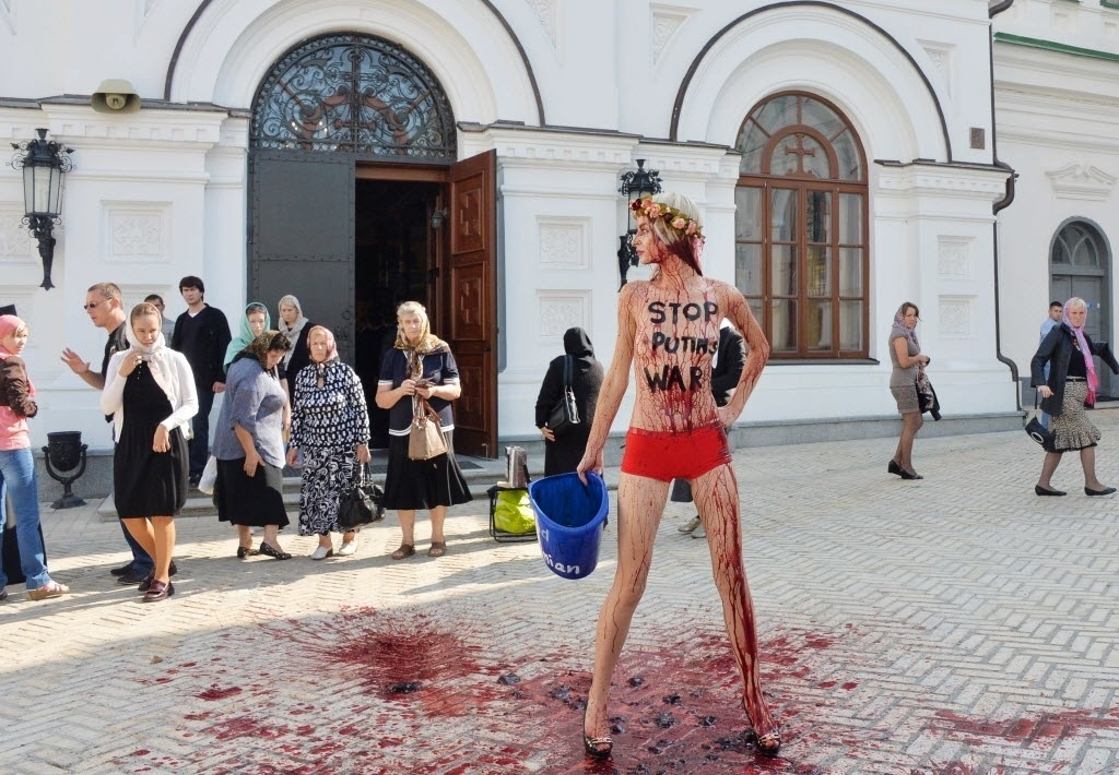 11.set.2014 - Religiosas observam ativista do Femen durante protesto em frente ao mosteiro de Pechersk Lavra em Kiev, na Ucrânia. A manifestação foi contra a ofensiva russa no país