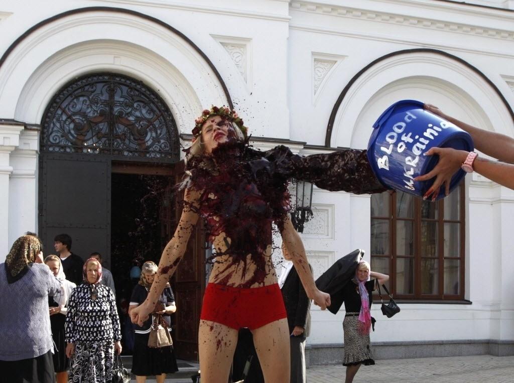 11.set.2014 - Ativista do Femen tem sangue falso jogado contra o corpo durante protesto em frente ao mosteiro de Pechersk Lavra em Kiev, na Ucrânia. A manifestação foi contra a ofensiva russa no país