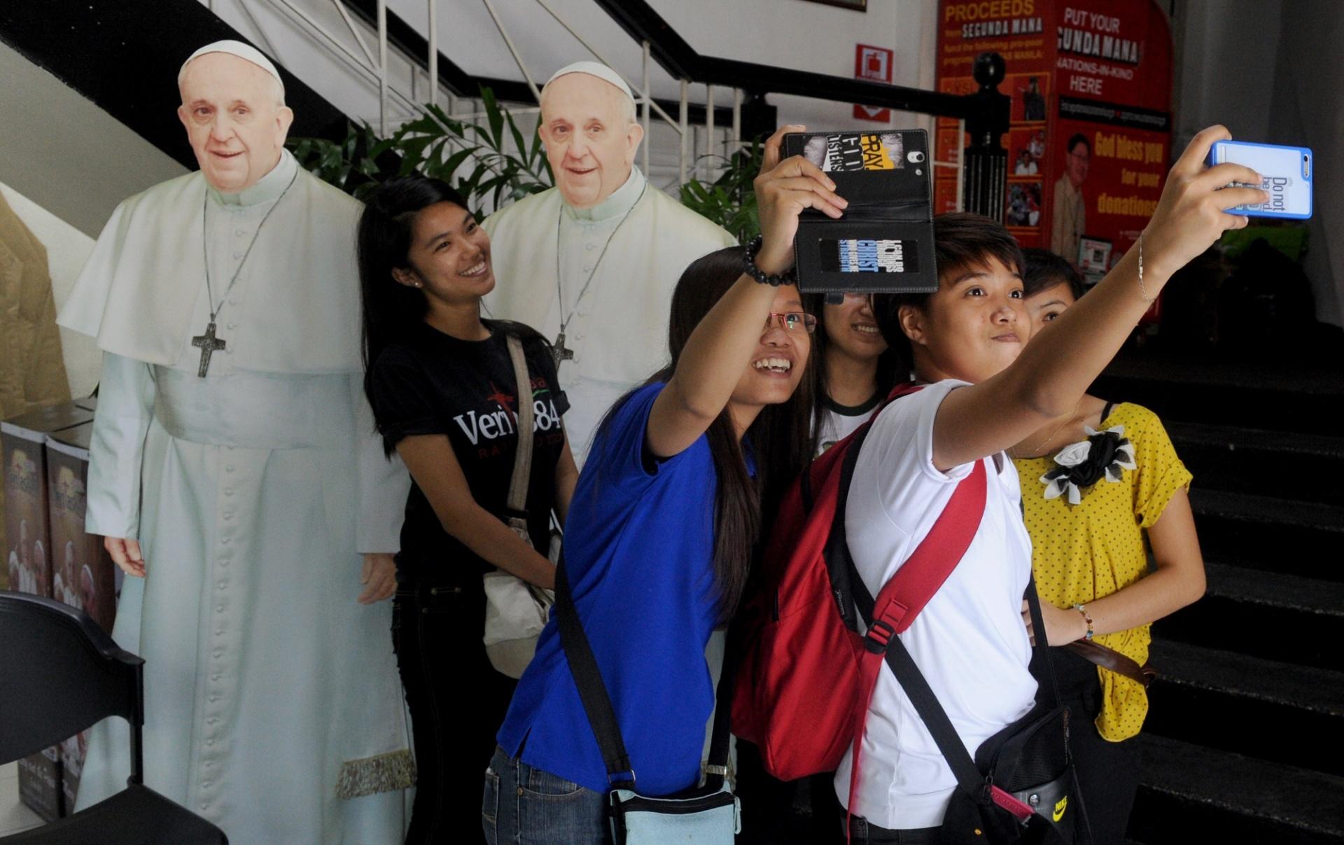 12.set.2014 - Garotas filipinas tiram selfies à frente de fotografias de papelão do papa Francisco, em uma estação de rádio católica no subúrbio de Manila. O papa vai visitar as Filipinas, um reduto católico da Ásia, em janeiro de 2015