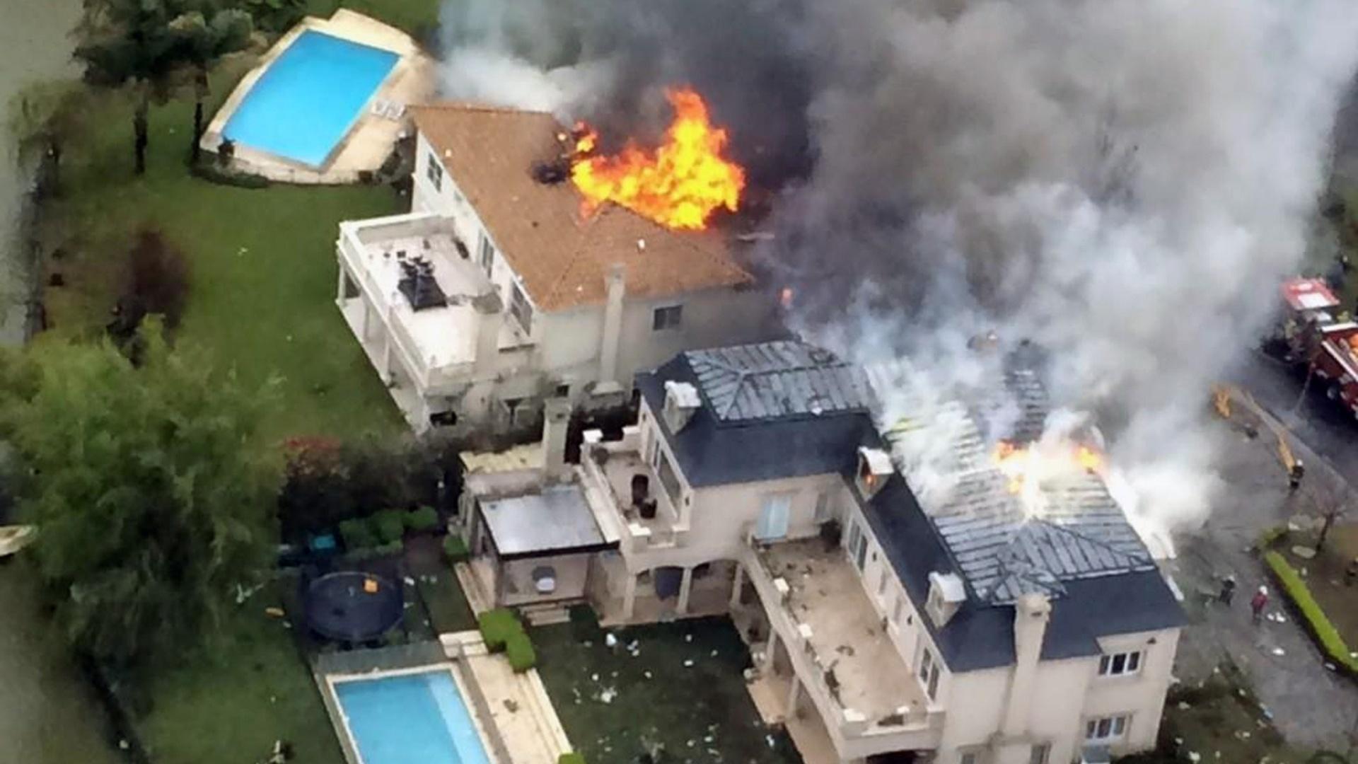14.set.2014 - Casas pegam fogo após um acidente aéreo em um condomínio fechado em Tigre, no norte da província de Buenos Aires, na Argentina, neste domingo (14). Ao menos uma pessoa morreu e outra ficou seriamente ferida após o acidente