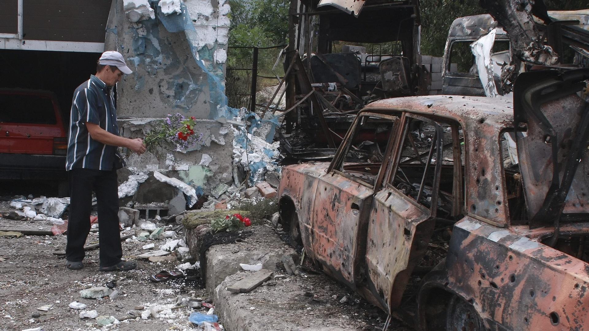16.set.2014 - Homem deposita flores no lugar em que oito pessoas morreram hoje, após um bombardeio em Donetsk, na Ucrânia. A ex-primeira ministra ucraniana Yulia Timoshenko acusa o presidente, Petró Poroshenko, de