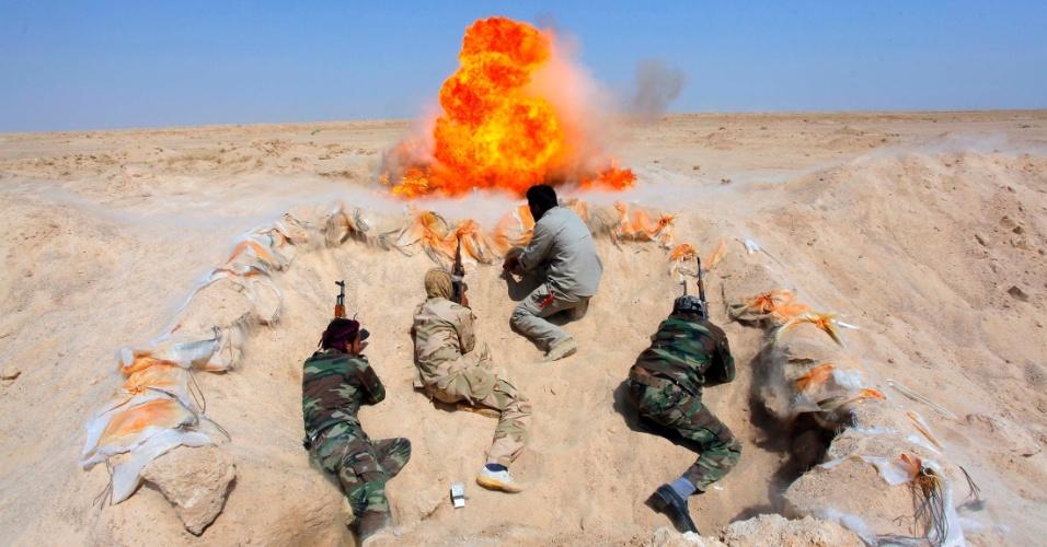 16.set.2014 - Homens participam de treinamento com bombas no deserto de Najaf, província iraquiana, após se alistarem ao Exército do país para combater o EI (Estado Islâmico)