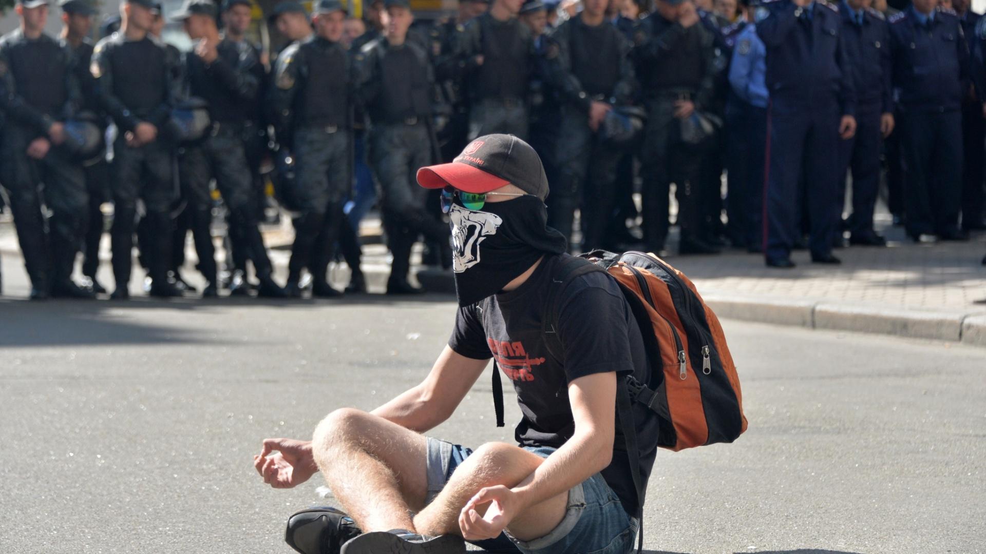 17.set.2014 - Ativista senta no chão na frente de uma barreira de policiais da Guarda Nacional da Ucrânia, que impede a entrada de manifestantes nesta quarta-feira (17) no palácio da presidência na capital Kiev