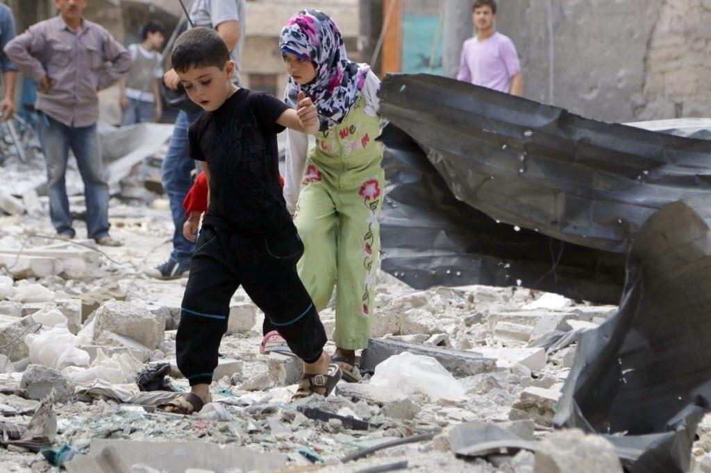 17.set.2014 - Crianças andam entre os escombros depois de um ataque aéreo feito por forças leais ao presidente da Síria, Bashar al-Assad, em Tal Al Zarazir, zona sul da cidade de Aleppo, nesta quarta-feira (17), de acordo com relato de ativistas locais