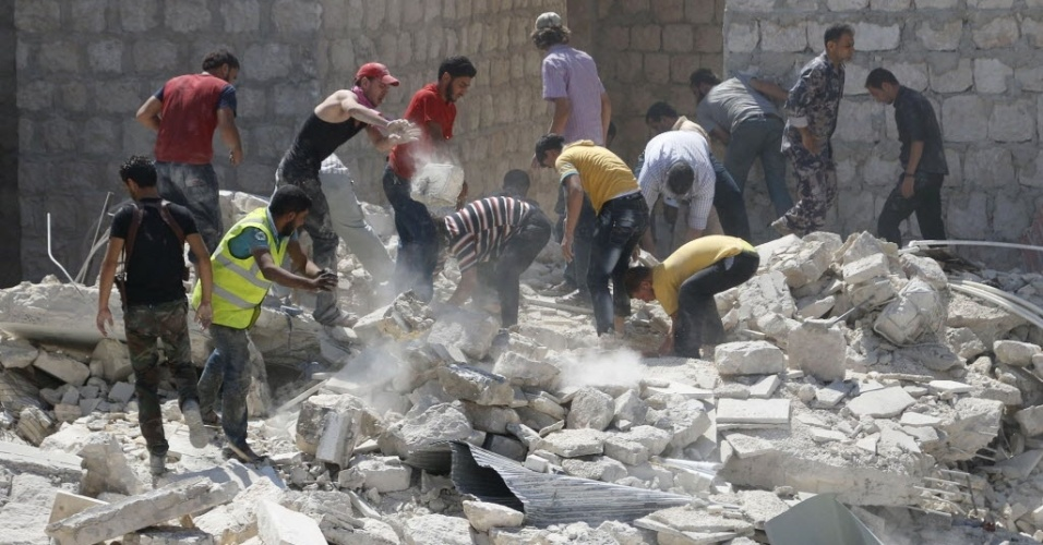 18.set.2014 - Moradores buscam sobreviventes sob os escombros de edifícios destruídos pela explosão de uma bomba, lançada pelas forças do ditador sírio Bashar Assad em Maarat Al-Nouman, sul de Idlib