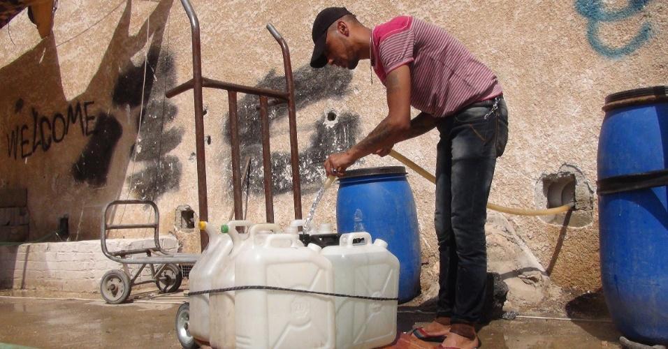 18.set.2014 - Sírio enche galões com água no campo de refugiados de Yarmouk, controlado pelas forças rebeldes, nesta quinta-feira (18). Segundo os militantes, o ditador Bashar Assad cortou o suprimento de água do local