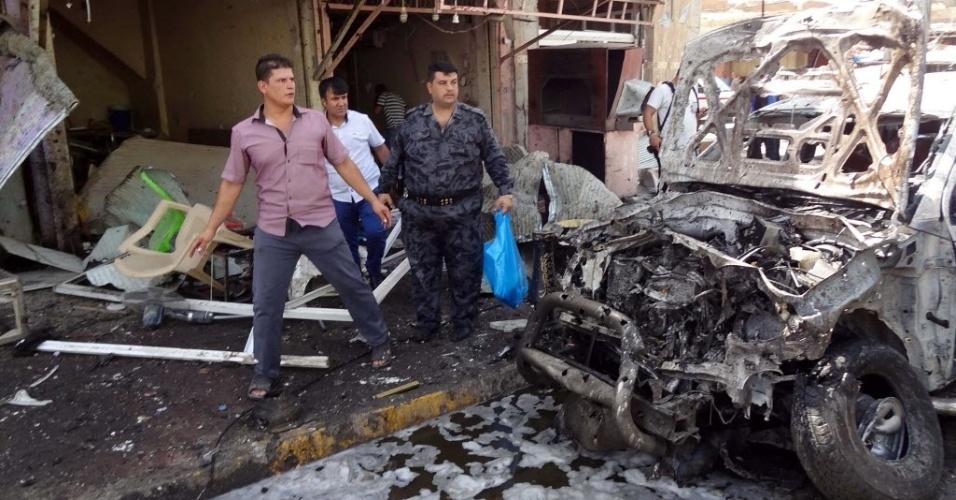 19.set.2014 - Iraquianos passam ao lado de um carro queimado após atentado a bomba que matou ao menos oito pessoas nesta sexta-feira (19), na cidade de Kirkuk, no Iraque. Os ataques acontecem enquanto as forças de segurança, milicianos xiitas e membros de tribos sunitas lutam para recuperar o terreno tomado pelo Estado Islâmico no país