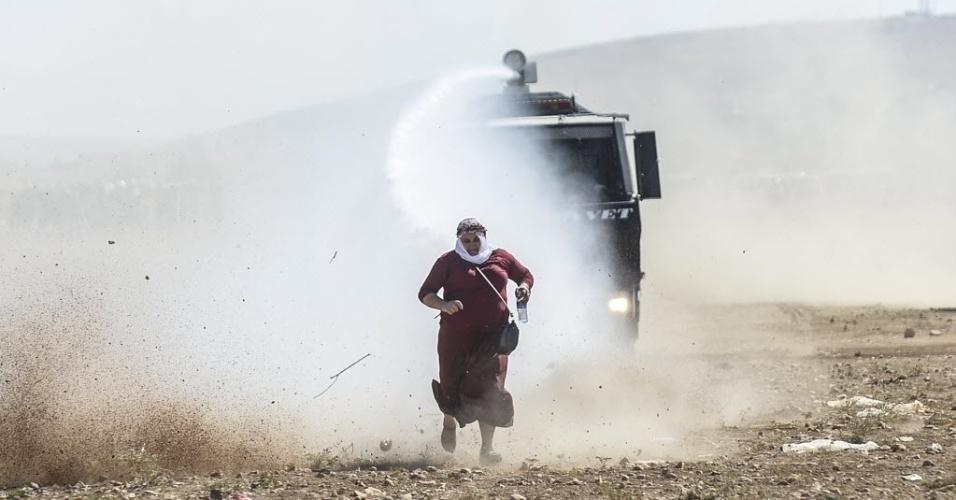 22.set.2014 - Uma mulher curda foge de um canhão de água perto da fronteira com a Síria depois que as autoridades turcas fecharam temporariamente a com a Síria, nesta segunda-feira (22), após receber uma onda de mais de 130 mil sírios, nos últimos dias, fugindo das perseguições do grupo radical Estado Islâmico