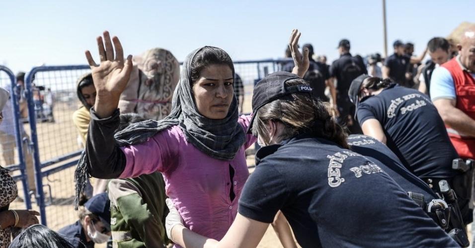 23.set.2014 - Mulher é revistada na fronteira entre a Síria e a Turquia na cidade de Suruc, na província de Sanliurfa. A ONU alertou que 400 mil pessoas devem tentar entrar na Turquia fugindo da violência do Estado Islâmico