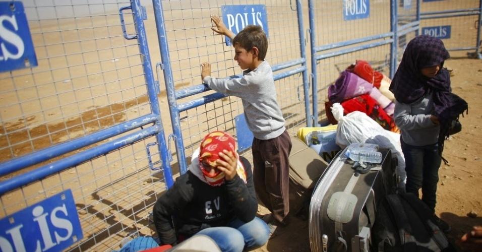 24.set.2014 - Refugiados curdos esperam para cruzar a fronteira entre a Síria e a Turquia na cidade de Suruc, na província de Sanliurfa. A ONU alertou que 400 mil pessoas devem tentar entrar na Turquia fugindo da violência do Estado Islâmico