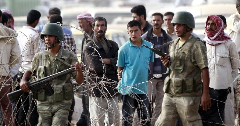 24.set.2014 - Refugiados sírios esperam para cruzar a fronteira entra a Síria e  Turquia na cidade de Suruc, na província de Sanliurfa. A ONU alertou que 400 mil pessoas devem tentar entrar na Turquia fugindo da violência do Estado Islâmico